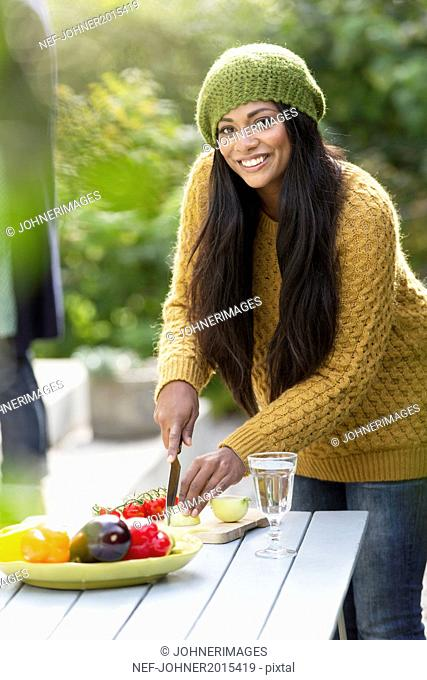Smiling young woman cutting vegetables