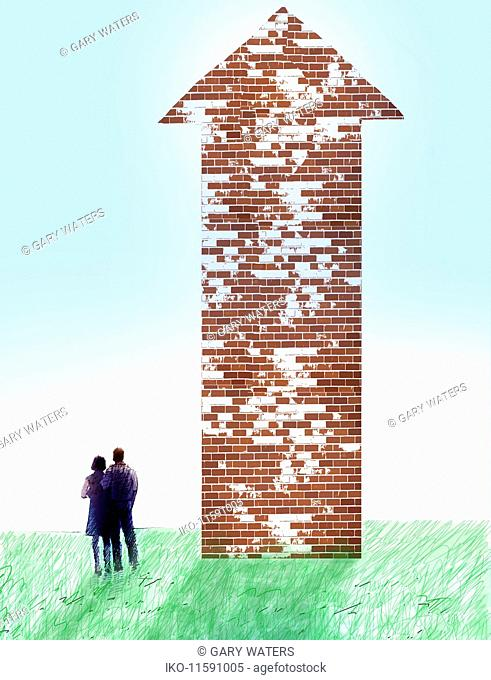 Couple looking at brick wall arrow