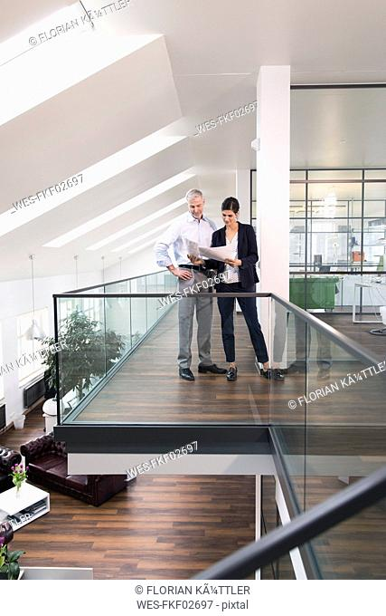 Colleagues standing in modern office, discussing documents