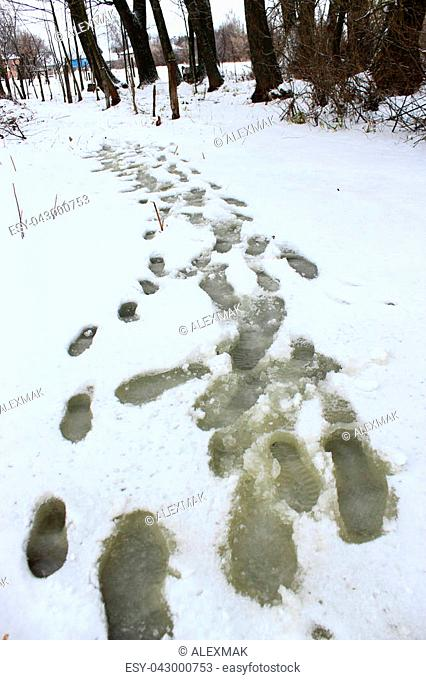 Traces of shoes on snow during the thaw. Footprints on the river ice