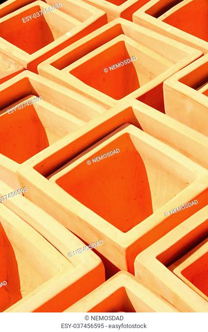An abstract composition of square terra cotta pots is featured