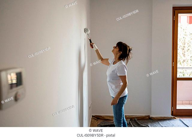 Senior woman painting house interior white wall with paint roller