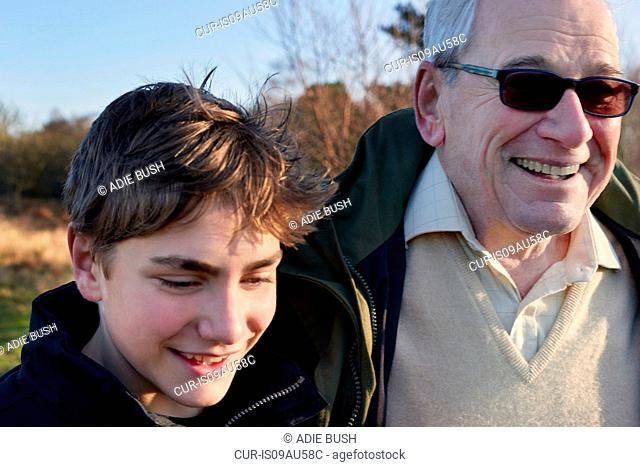 Grandfather and grandson walking through field
