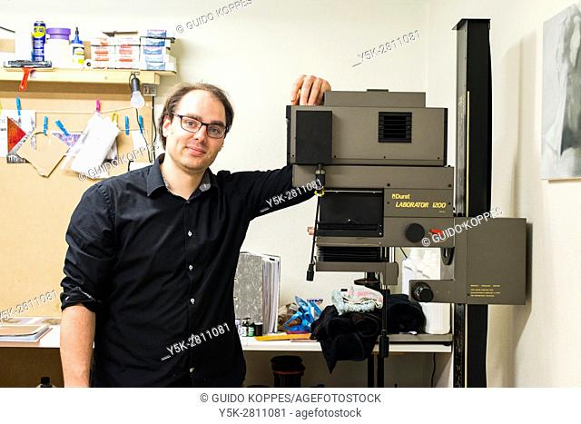 Tilburg, Netherlands. Portrait of a photographic artist inside his studio and darkroom with his vintage Durst magnifier and optical printer
