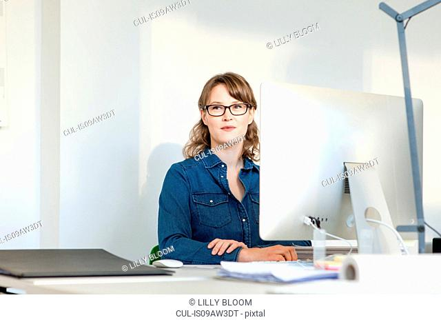 Young woman wearing eyeglasses sitting at desk using computer looking away smiling