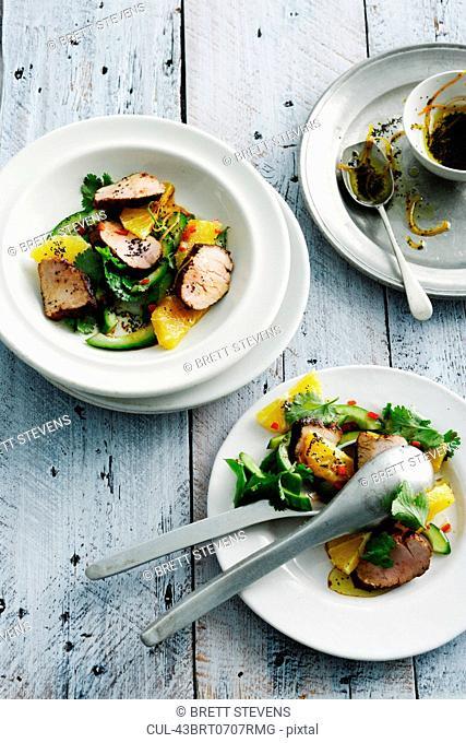 Plates of pork and orange salad