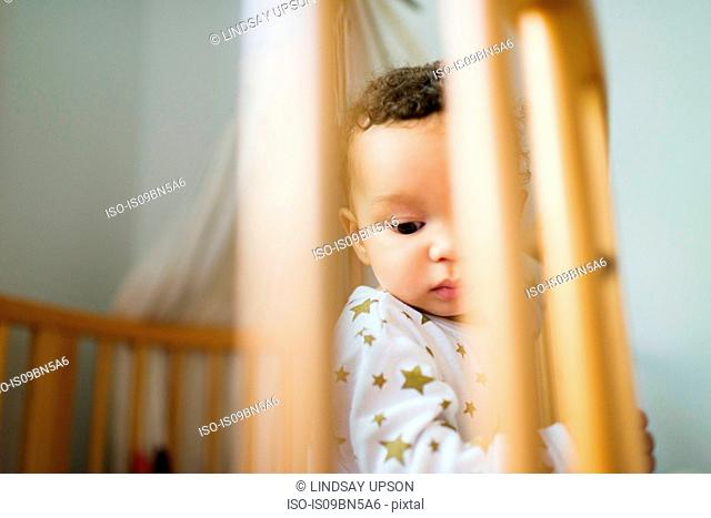 Baby boy standing up in crib looking down