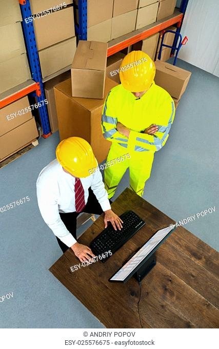 Elevated View Of Warehouse Worker And Manager Using Computer In A Warehouse
