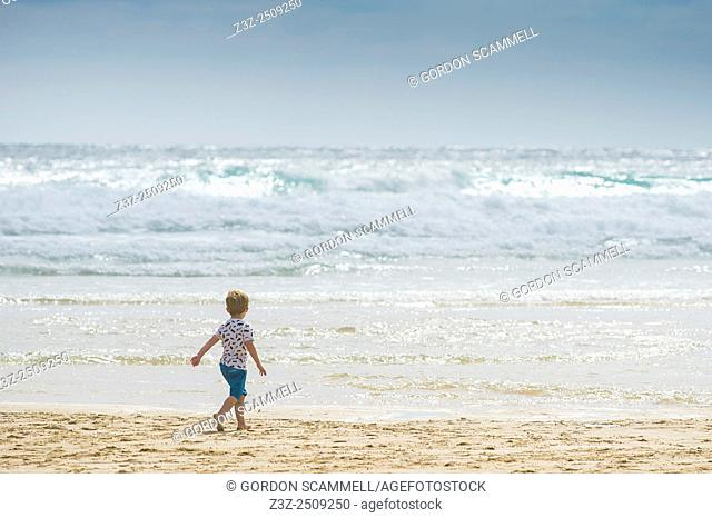 A young boy plays on Fistral Beach in Newquay, Cornwall, UK