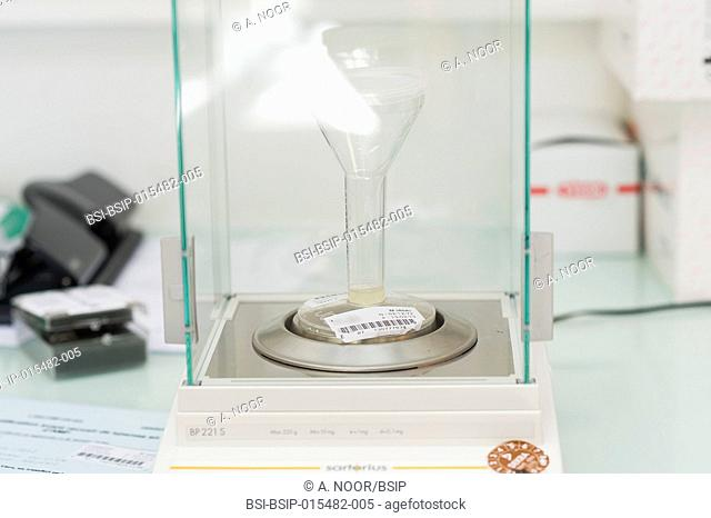 Reportage in the reproductive biology service in Nice hospital, France. In the spermatology lab: weighing a vial of sperm to determine the weight of each...