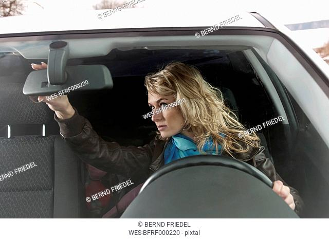 Germany, Brandenburg, Woman looking in rearview mirror