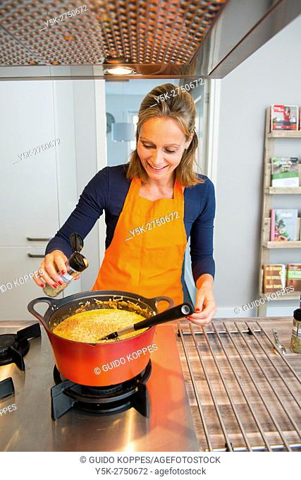 Kaatsheuvel, Netherlands. Mid adult woman adding a herbs and spices to her red colored saucepan, in preparation of a Lasagna dish dinner