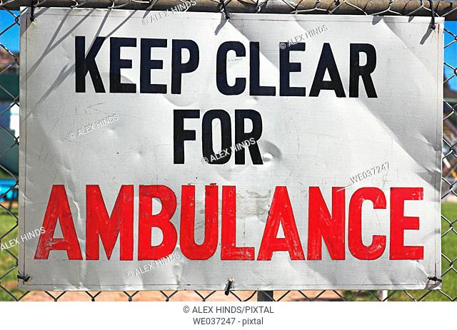 Sign on fence requesting clear access for ambulance / emergency use