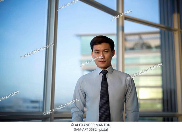 Singapore, Indoor portrait of businessman standing in front of window