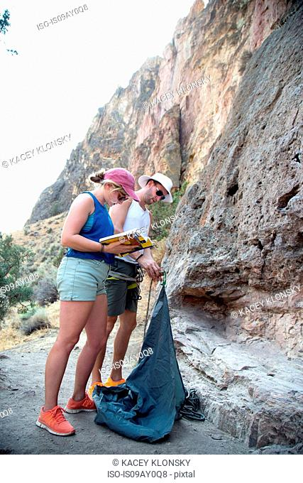 Couple at rock face with climbing equipment reading book