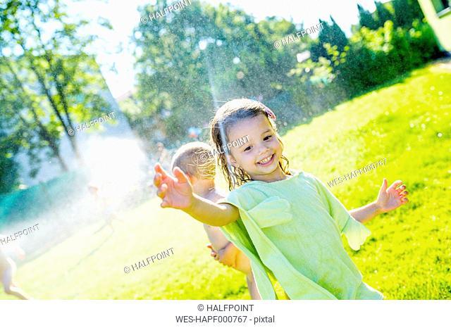 Little girl having fun with lawn sprinkler in the garden