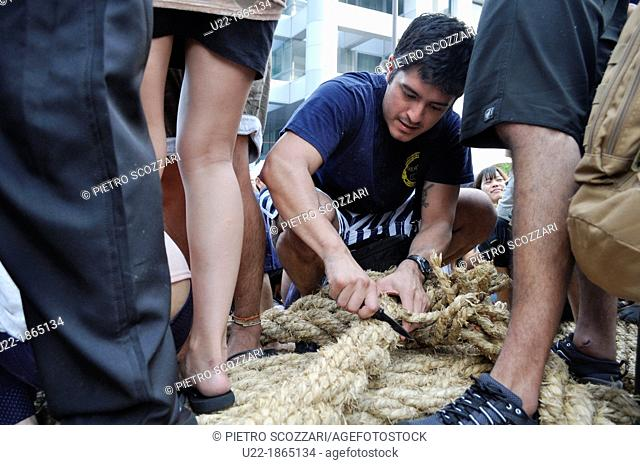 Naha, Okinawa, Japan, American soldier cutting rope for good luck along the Route 58 during the Tug of war Festival, October