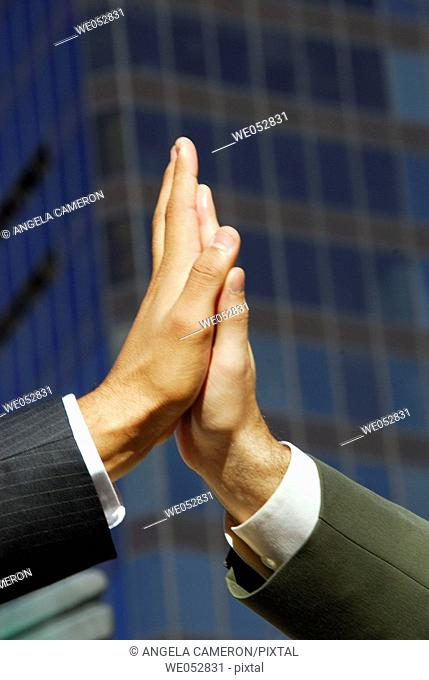 2 young male business men putting hands together with building in background