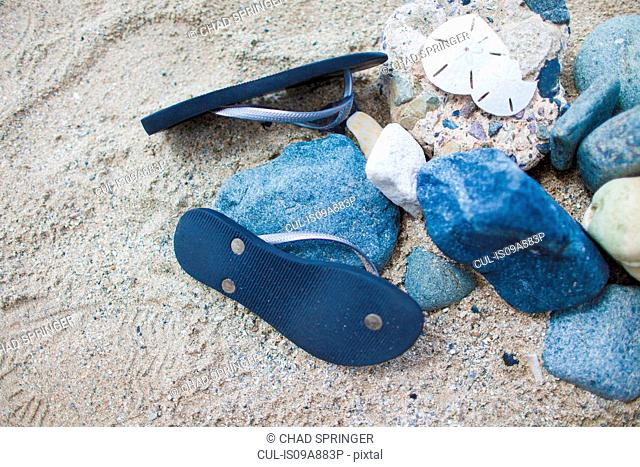 Pair of blue flip flops on sand