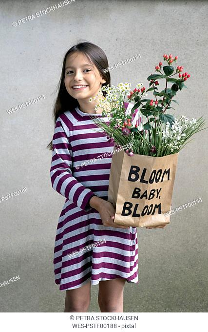 Portrait of smiling girl holding paper bag with flowers