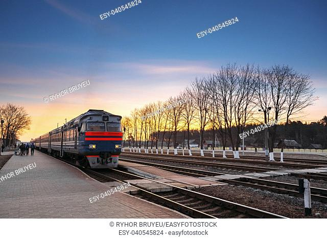 Arriving old train diesel locomotive in a railway station in Belarus. Morning sunset, colorful sky