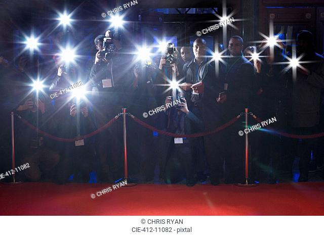 Paparazzi using flash photography behind rope on red carpet