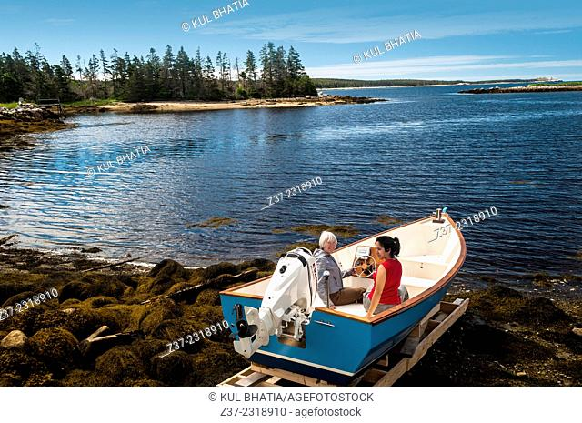 Mother and daughter sitting in a brand new boat about to be launched, Halifax, Canada
