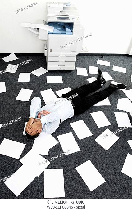 Businessman lying among slips of paper, hands to face