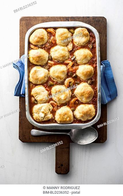Dumplings gumbo in pan on cutting board