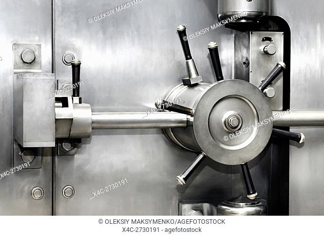 Shiny stainless steel bank vault safe door lock. Banking, security, investment concept
