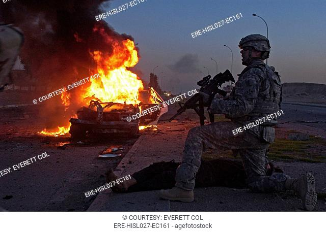 US Army soldier yells for a medic to treat an Iraqi civilian injured in a car bomb explosion in Mosul Iraq. March 6 2008. BSLOC-2011-12-166