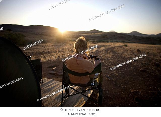 Rear view of woman at sunset, pouring wine, Sesfontein, Kaokoland, Namibia