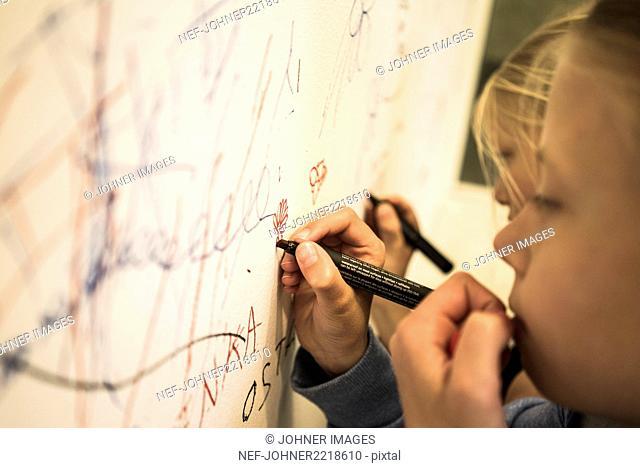 Girls writing on wall