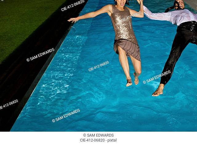 Fully dressed couple jumping into swimming pool