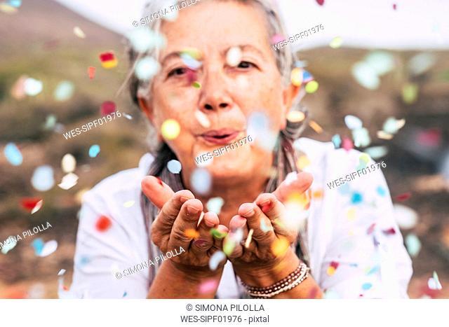 Senior woman blowing confetti outdoors