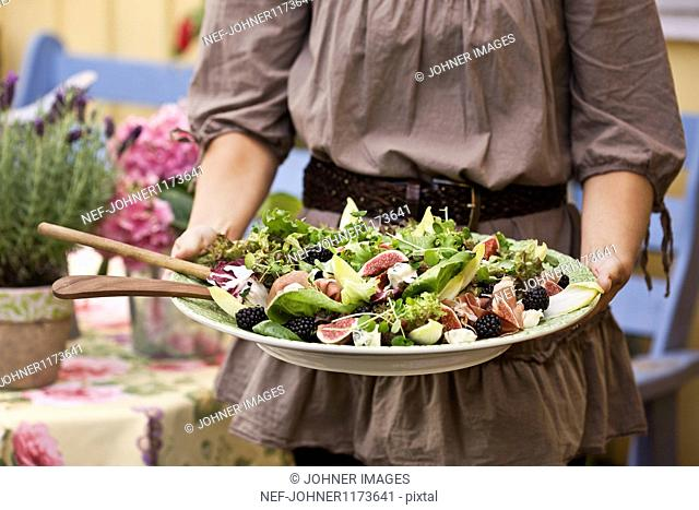 Woman holding plate of salad, close-up, mid section