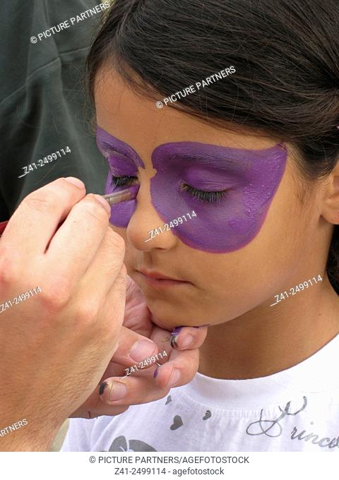 Little girls face is painted with purple paint