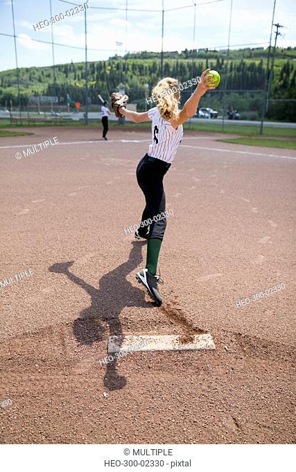 Middle school girl softball pitcher pitching ball on baseball diamond