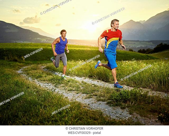 Two athletes running on field path at sunset
