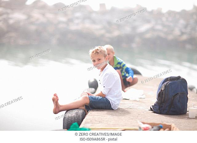 Two young boys sitting on pier fishing