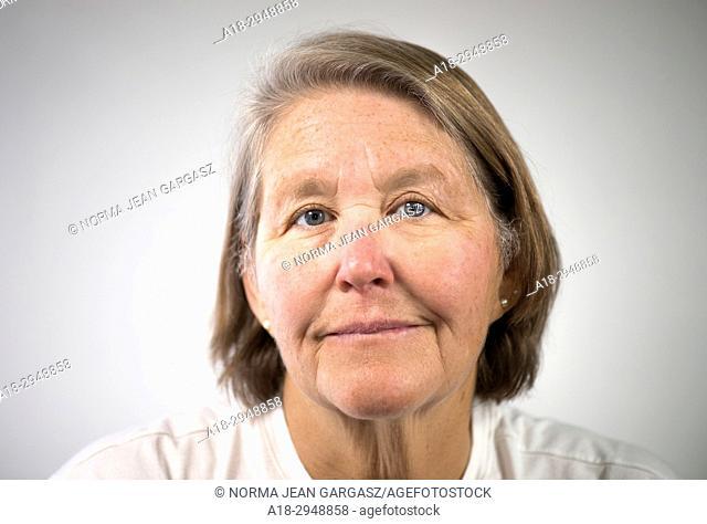A senior citizen female poses for a portrait