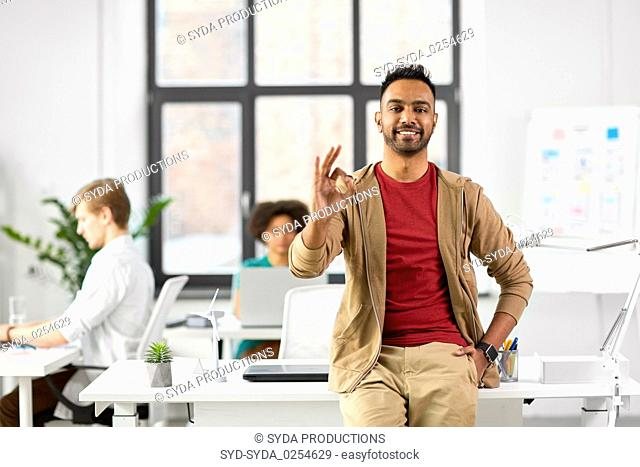 smiling indian man showing ok hand sign at office