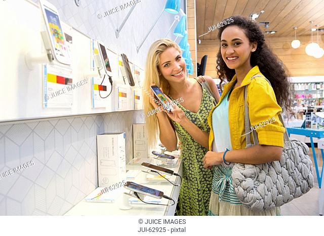 Young female friends shopping in phone store