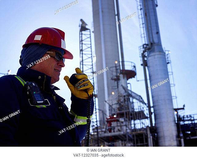 Tradesman talking into a radio while working at a refinery; Edmonton, Alberta, Canada