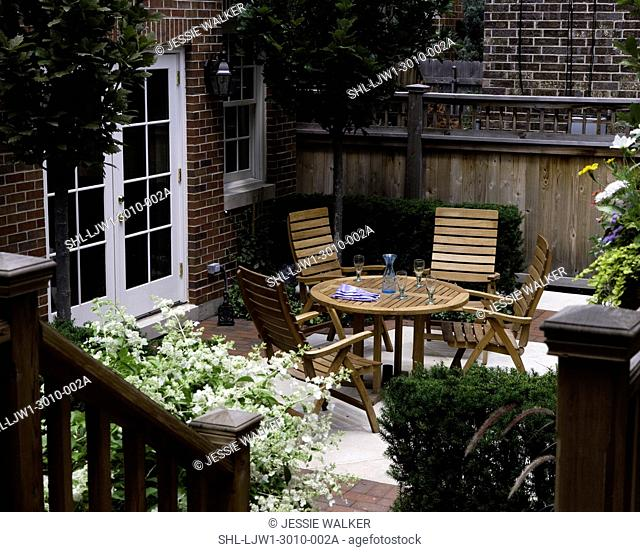 PATIO: City garden, wooden privacy fence, brick garage with french doors, teak patio set, looking down from deck area, pin oaks
