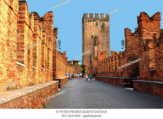 Pedestrian path on the Castelvecchio bridge Ponte Scaligero over the river Adige in Verona with view of the main tower - Italy