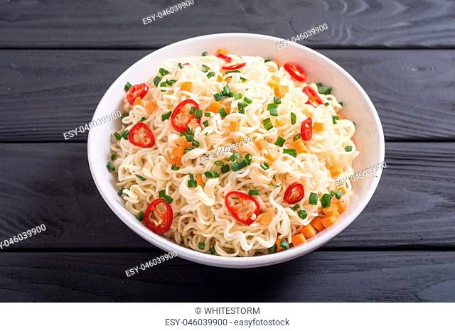 Instant noodles in bowl with chili peppers , onion and carrots