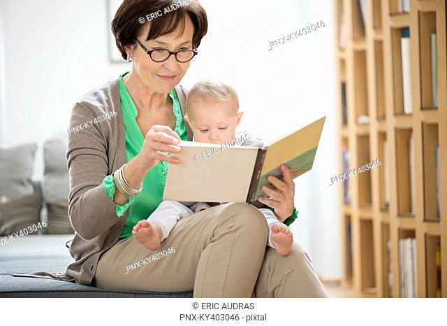 Woman with her granddaughter reading a picture book