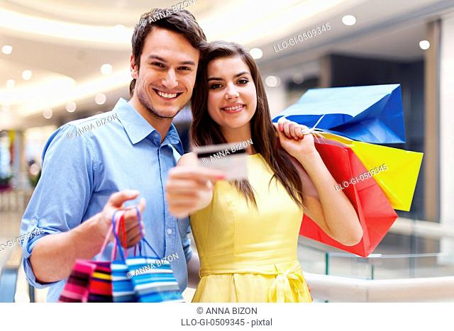Beautiful couple showing credit card in the shopping mall Debica, Poland