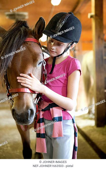 Girl with horse in stable